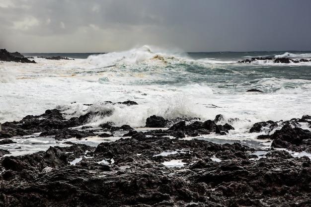 Duże Fale Rozbijające Się W Pobliżu Skalistego Brzegu. Burza Oceaniczna Premium Zdjęcia