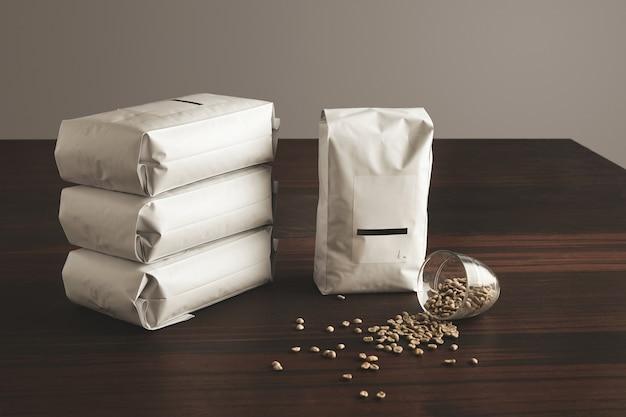 Duże hermetyczne opakowanie z pustą etykietą, prezentowane obok czterech innych leżących woreczków wypełnionych paloną kawą