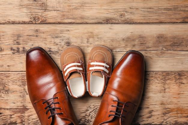 Duże i małe buty na drewnianym. kompozycja na dzień ojca