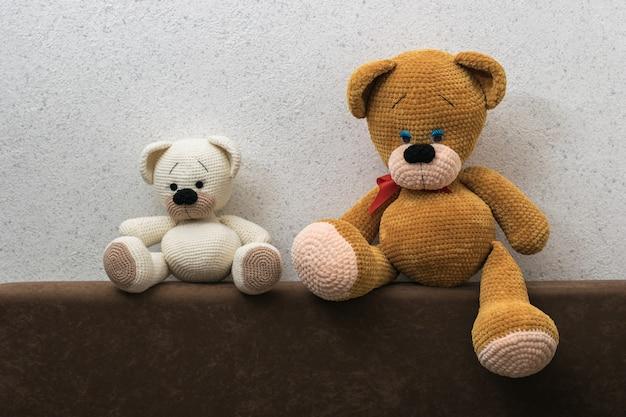 Duże i małe misie z tyłu sofy w pobliżu teksturowanej ściany. piękna dzianinowa zabawka.