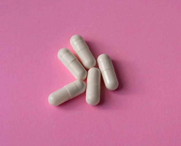 Duże kapsułki na różowym tle