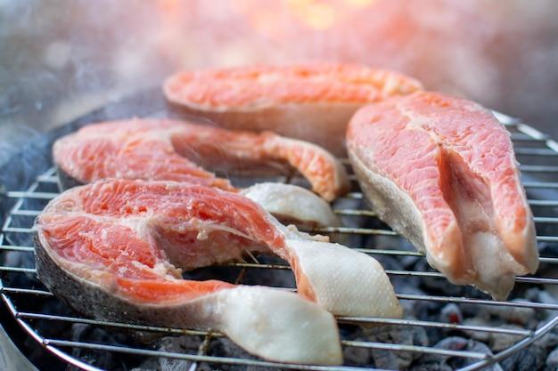 Duże kawałki czerwonej ryby leżą na grillu, grillu łososia, z bliska