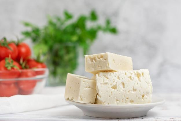 Duże kawałki sera feta na białym talerzu i pomidorki koktajlowe na świetle.