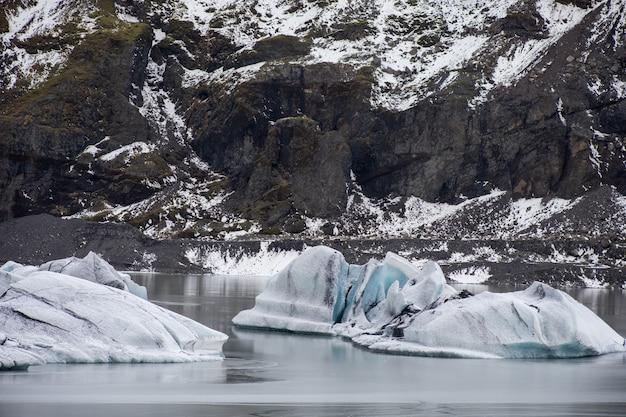 Duże kawałki słodkowodnego lodu w zamarzniętym jeziorze otoczonym skalistymi górami