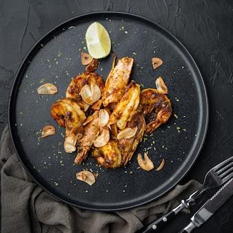 Duże krewetki bbq z grilla ze słodkim sosem mango i zestawem curry, na talerzu, na czarno