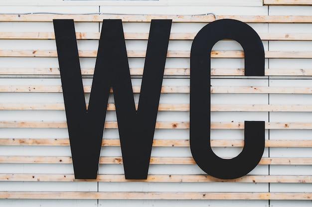 Duże litery wc na elewacji budynku z boazerią. znak toalety publicznej w parku miejskim. międzynarodowy symbol toalety. wc na zewnątrz, ubikacja.