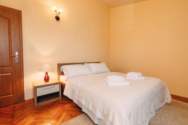 Duże łoże małżeńskie z poduszkami i puszystymi ręcznikami na narzucie w przestronnym pokoju