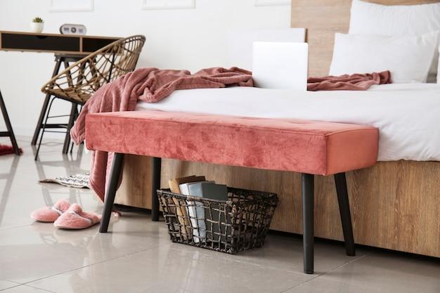 Duże łóżko i ławka we wnętrzu nowoczesnego pokoju