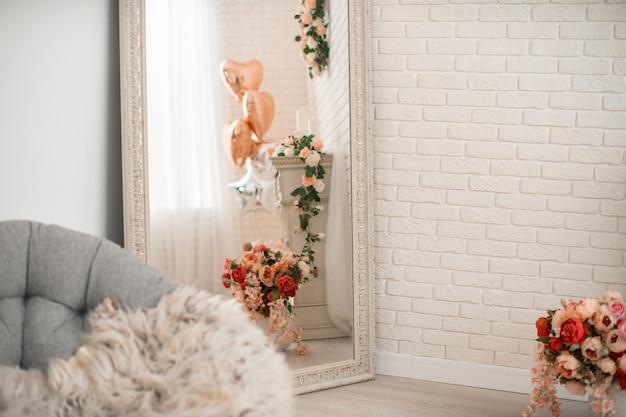 Duże lustro w pięknej ramie, refleksyjny kominek ozdobiony kwiatami