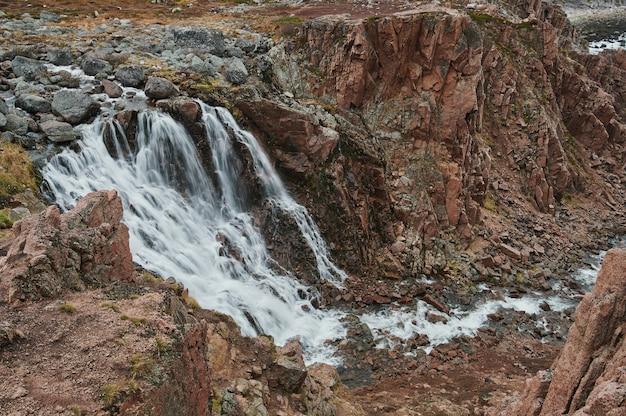 Duże naturalne kamienie schodkowe w poprzek płynącego strumienia rzeki, kanału jeziora, spokojny, spokojny, relaksujący spacer na świeżym powietrzu