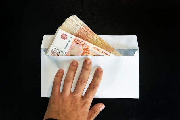 Duże nominały 5000 rubli w białej kopercie. ręka mężczyzny trzyma kopertę z pieniędzmi. pojęcie przekupstwa i korupcji. gotówka, przepływ gotówki