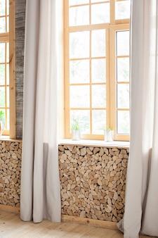 Duże okna świetlików z drewnianymi wykończeniami i zasłonami. piękny poranek. dużo powietrza, lekkości i wygody. pusty pokój, drewniane okno z zasłoną. hygge. boho rustykalne wnętrze. skandynawski wystrój