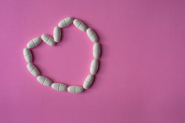Duże pigułki lub tabletki, ułożone w kształcie serca