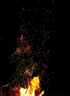 Duże płonące ognisko z płomieniem i pomarańczowymi iskrami, które latają w różnych kierunkach