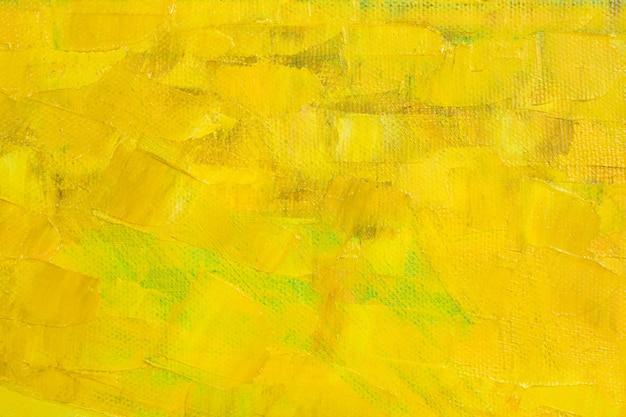 Duże pociągnięcia różnych odcieni żółtej farby olejnej na powierzchni płótna.