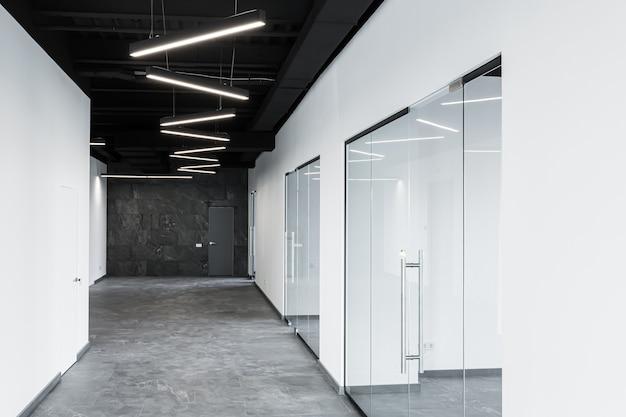 Duże przestronne centrum biurowe z panoramicznymi oknami i nieumeblowanymi szklanymi drzwiami