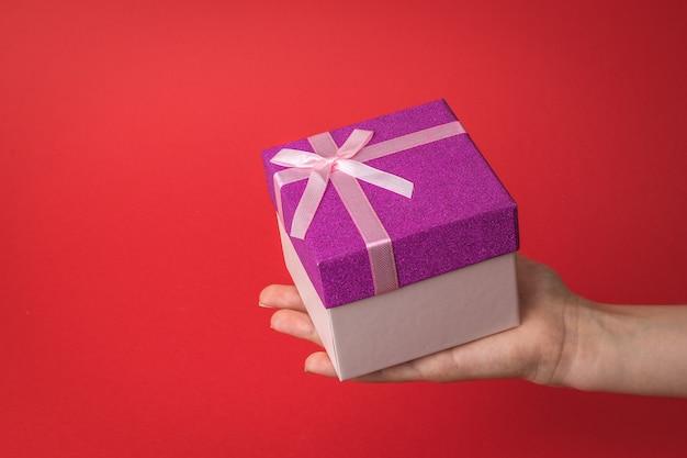 Duże pudełko prezentowe w dłoni dziecka na czerwonym tle. niespodzianka w rękach dziewczynki.