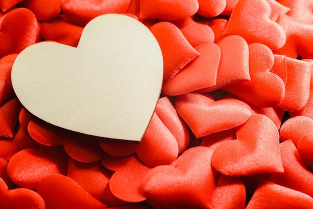 Duże puste drewniane serce otoczone małe czerwone serca na walentynki, wolne miejsce na tekst.