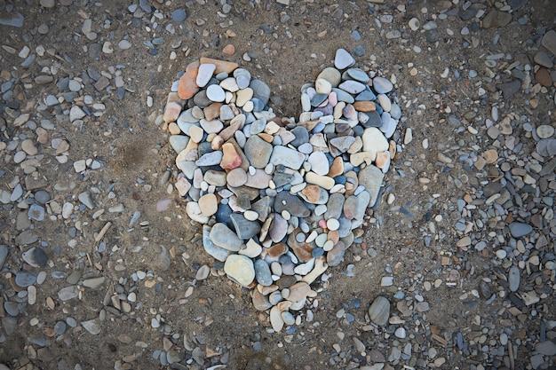 Duże serce z małych kamyków nad brzegiem morza