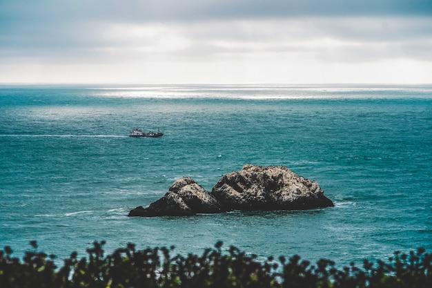 Duże skały na środku morza i oddalona żegluga straży przybrzeżnej