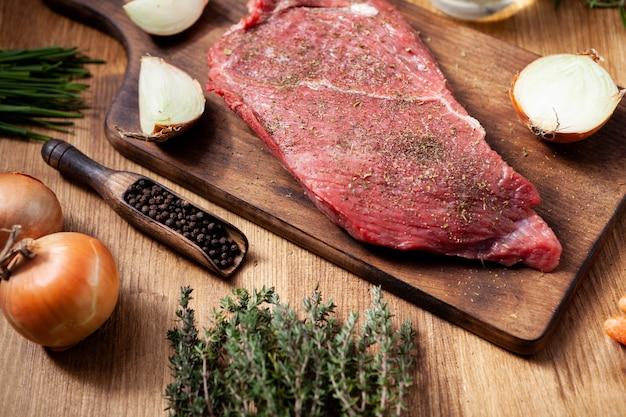 Duże smaczne surowe mięso na desce do krojenia z rozmarynem. czarny pieprz. przyprawa