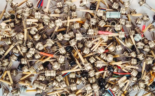 Duże sterty starych tranzystorów na białym tle