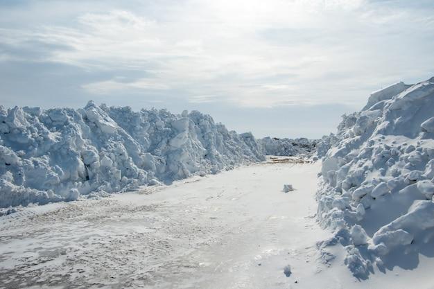 Duże stosy śniegu na poboczu drogi dla samochodów, wysokie zaspy śnieżne po opadach śniegu lub zamieci