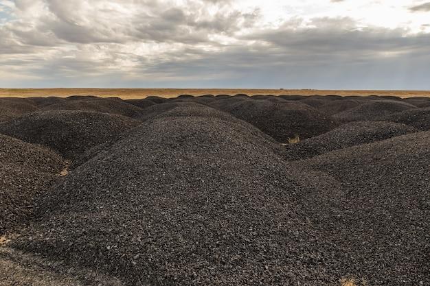 Duże stosy starego asfaltu na stepie po remoncie drogi kazachstan