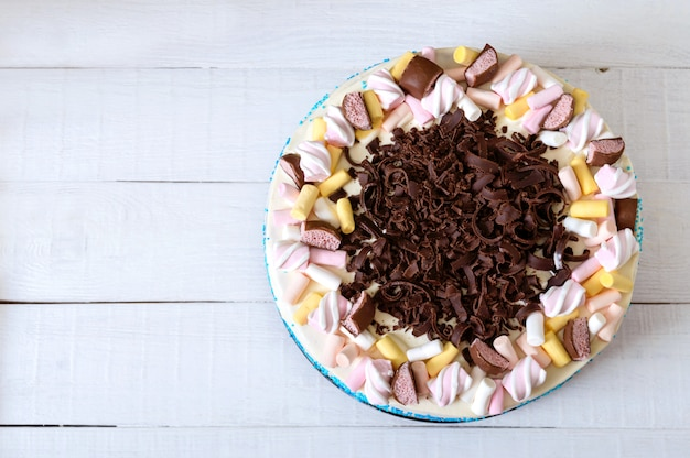Duże świąteczne ciasto ozdobione kawałkami czekolady, pianki. skopiuj miejsce na napisy. widok z góry, leżał płasko.