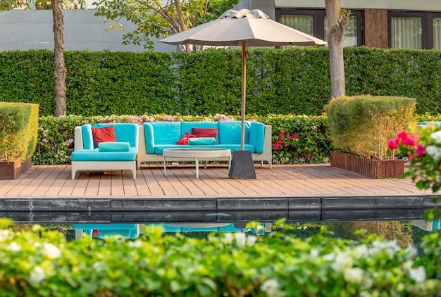 Duże tarasowe patio z meblami z rattanu w ogrodzie z parasolem.