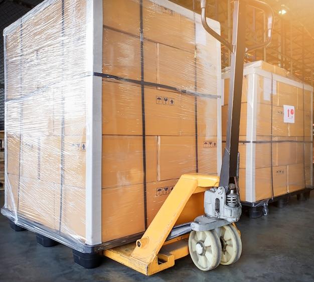 Duże towary paletowe i żółty ręczny wózek paletowy. magazyn towarów eksportowo-wysyłkowych,