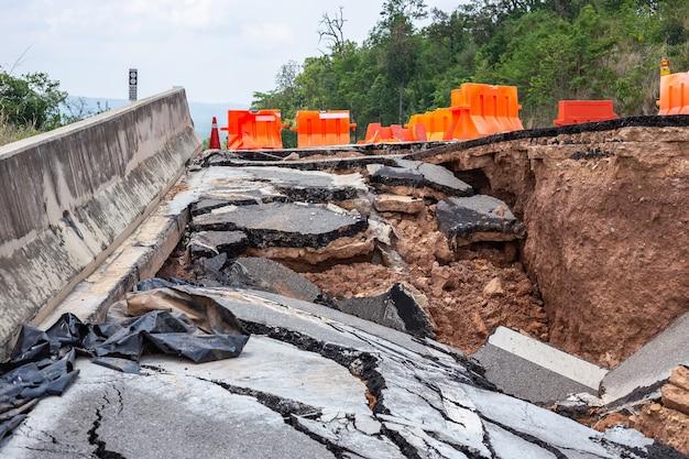 Duże uszkodzenia drogi asfaltowej na zboczu wzgórza powodują ulewny deszcz i przesuwającą się ziemię