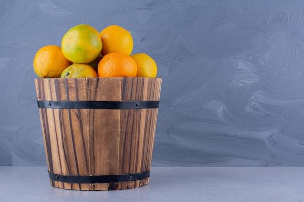 Duże wiadro mandarynek na marmurowym tle. zdjęcie wysokiej jakości