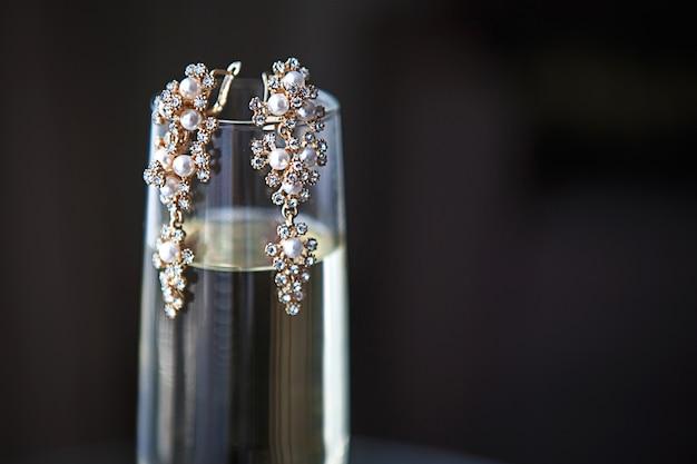 Duże złote kolczyki z perłami i kryształkami na przezroczystym kieliszku szampana.