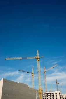 Duże żurawie wieżowe nad budowanymi budynkami