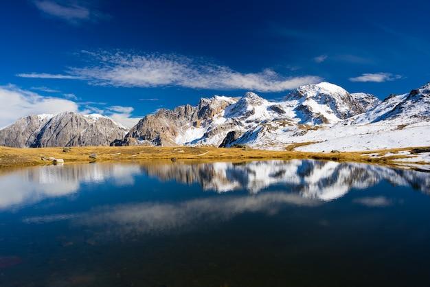 Dużej wysokości niebieskie alpejskie jezioro w sezonie jesiennym