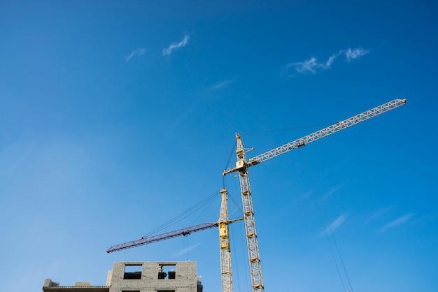 Duzi żurawie wieżowe nad budynki w budowie przeciw niebieskiemu niebu. tło wizerunek budowy zakończenie z kopii przestrzenią. budowa miasta.