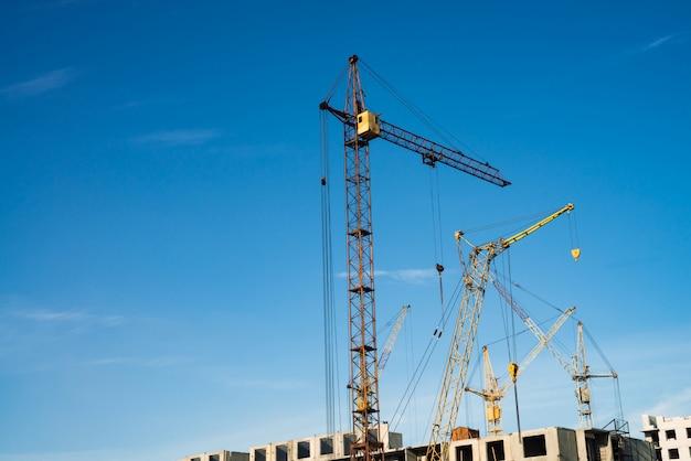 Duzi żurawie wieżowe nad budynki w budowie przeciw niebieskiemu niebu. wizerunek budowy zakończenie z kopii przestrzenią. budowa miasta.