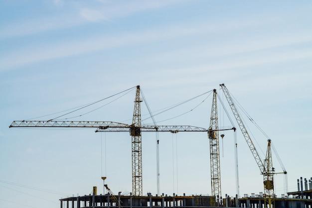 Duzi żurawie wieżowe nad budynki w budowie przeciw niebieskiemu niebu.