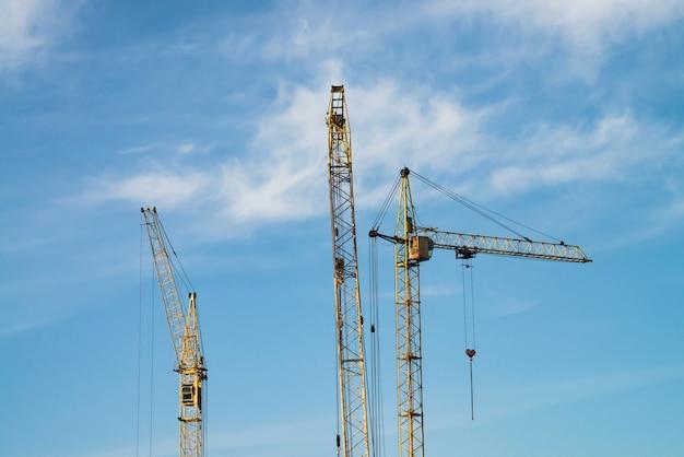 Duzi żurawie wieżowe przeciw niebieskiemu niebu. wizerunek budowy wyposażenia zakończenie z kopii przestrzenią. budowa miasta.