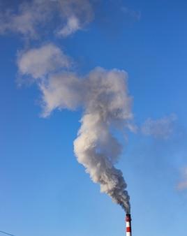 Dużo białego dymu wydobywa się z dużej, wysokiej ceglanej elektrociepłowni. zimą na tle czystego, błękitnego nieba. sytuacja ekologiczna we wsi. emisja substancji odpadowych.