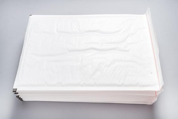 Dużo białych bąbelków kopert na szarym tle