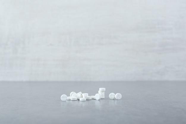 Dużo białych tabletek kółek na szarej powierzchni