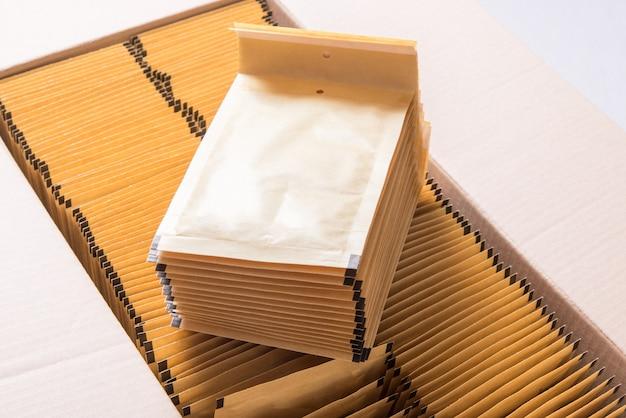 Dużo brązowej koperty pocztowej w kartonowym pudełku