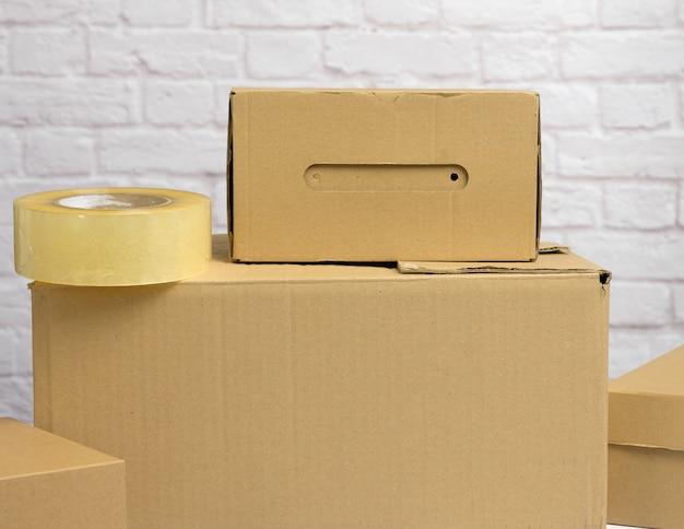Dużo brązowych pudeł kartonowych, proces pakowania rzeczy w ruchu, z bliska