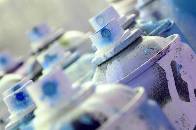 Dużo brudnych i zużytych puszek z aerozolem z jasnoniebieską farbą.