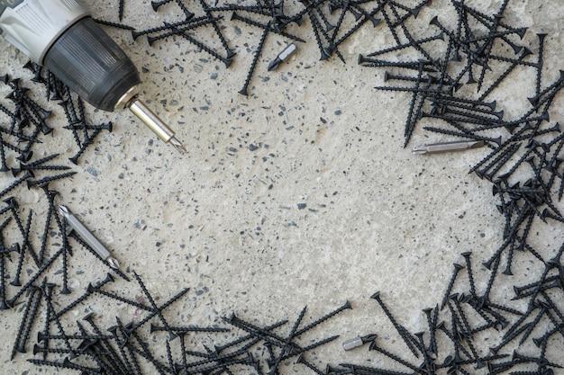 Dużo czarnych metalowych śrub na betonowej powierzchni