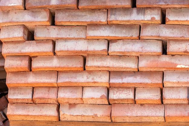 Dużo czerwonych cegieł ceramicznych w tle na budowie, placu budowy