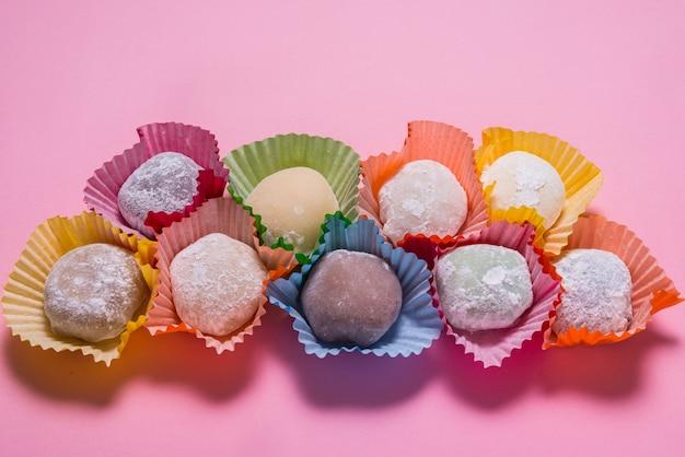 Dużo deseru mochi w papierowych filiżankach na różowym stole