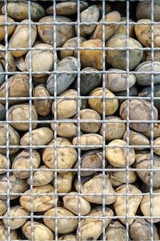 Dużo kamienia w stalowej kratce z drutu na tle.